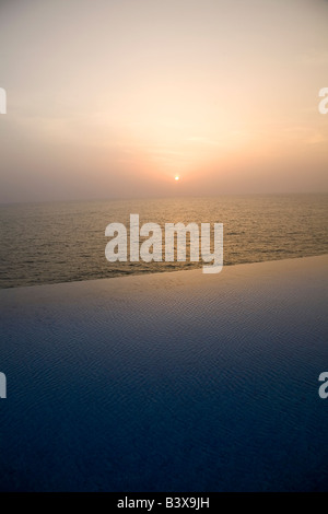 A infinity swimming pool overlooks the Arabian Sea at Kovalam Beach in Kerala, India. - Stock Photo