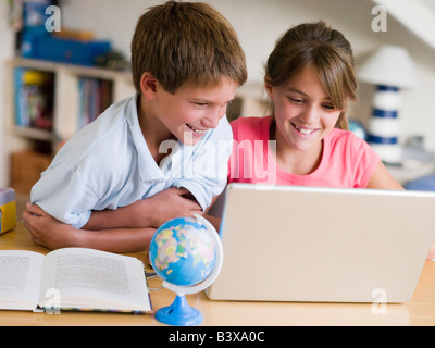 Boy And Girl Doing Their Homework On A Laptop - Stock Photo