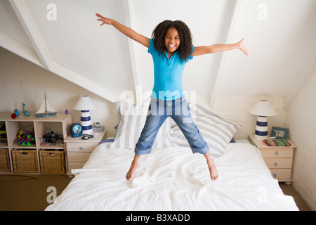 Young Girl Jumping On Her Bed - Stock Photo