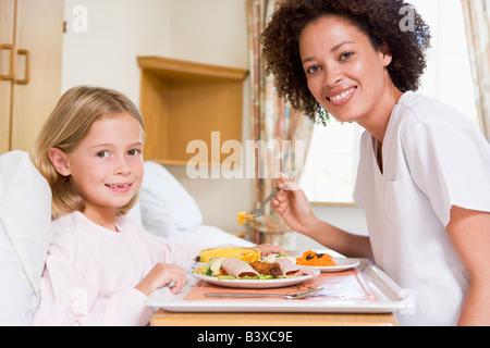 Nurse Feeding Young Girl - Stock Photo