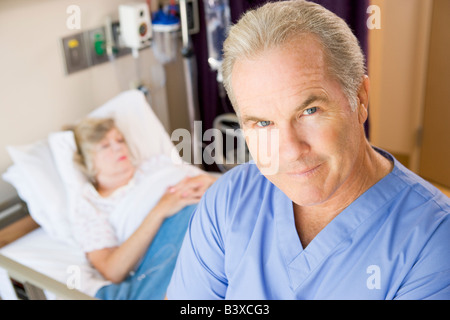 Doctor Standing In Patients Room, Looking Serious - Stock Photo