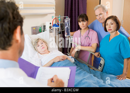 Doctor Making Notes On Patient - Stock Photo
