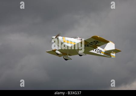 Vans RV-6A G-RVDR in flight aginst a dark sky after taking-off from Breighton Airfield - Stock Photo