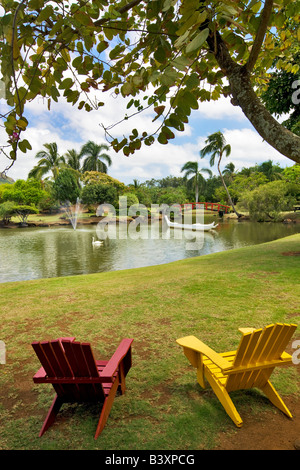Two chairs overlooking boat and swan on pond at Smith s Tropical Gardens Kauai Hawaii - Stock Photo