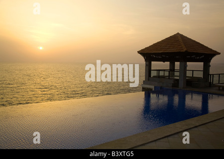 An infinity pool overlooks the Arabian Sea at Kovalam Beach in Kerala, India. - Stock Photo