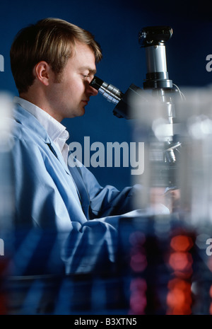 Technician checking water samples through a microscope in the quality control laboratory of a water treatment plant. - Stock Photo