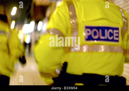 back of police officer on patrol at night - Stock Photo
