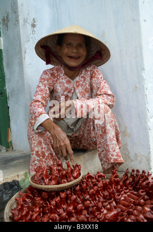 A local woman wearing a coolie hat selling souveniers to tourists in the village of Hoi An, Vietnam - Stock Photo