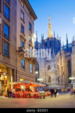 People dining at an outdoor cafe and people shopping. Piazza Del Duomo, Milan, Italy. - Stock Photo