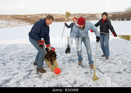 Family playing broomball with their dog - Stock Photo