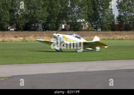 Vans RV-6A G-RVDR landing at Breighton Airfield and dragging tail along runway - Stock Photo