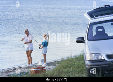 Mother and daughter together, mom teaching daughter to fish, laughing, having fun together, - Stock Photo