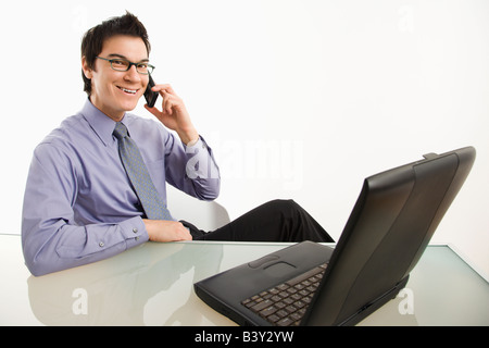 Smiling Asian businessman sitting at desk talking on cellphone - Stock Photo