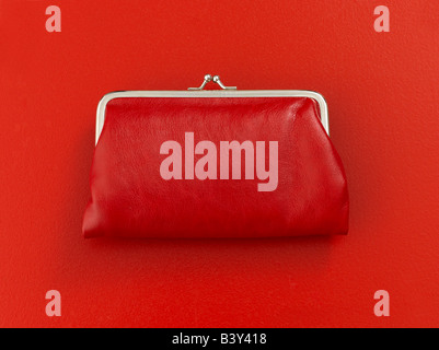 Red coin purse on red background - Stock Photo