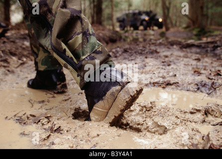 Close up of boot in mud of a USA Army soldier on maneuvers in the field - Stock Photo