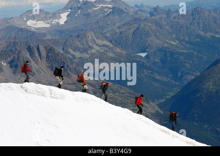 Mountaineers descend into the Vallee Blanche from the summit of the Aiguille du Midi cable car, Chamonix, French - Stock Photo