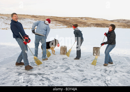 Family playing broomball - Stock Photo