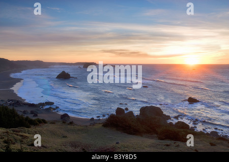 Sunset and waves off Blacklock Point with Cape Blanco in background Oregon - Stock Photo