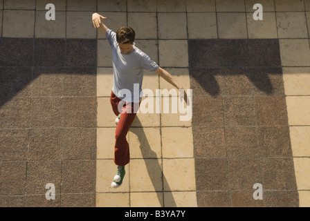Young man juggling a tennis ball on his foot on a Parisian street - Stock Photo