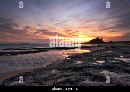 Sunrise on the deserted beach at Bamburgh with the castle in the distance - Stock Photo