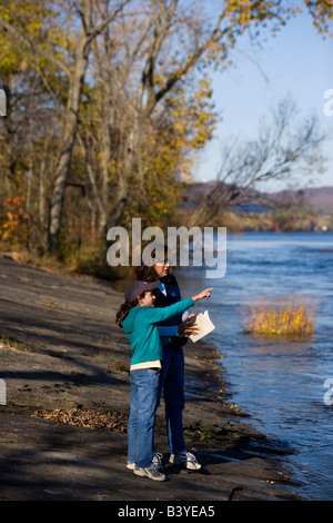 A mom and her daughter birdwatching on the banks of the Connecticut River in Holyoke, Massachusetts - Stock Photo