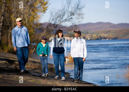 A family walks along the banks of the Connecticut River in Holyoke, Massachusetts - Stock Photo