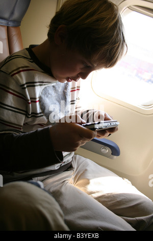 nine year old boy playing video game on airplane - Stock Photo