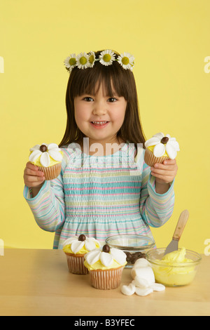 Little girl decorating cupcakes - Stock Photo