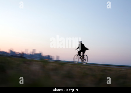 Man in suit rides bicycle along Chicago lakefront - Stock Photo