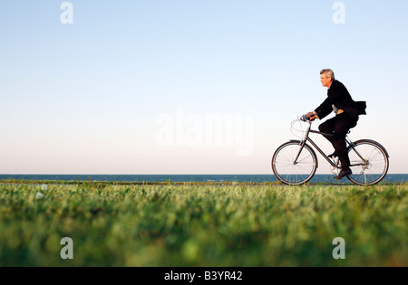 Man in suit rides bicycle along Chicago lakefront at dusk - Stock Photo