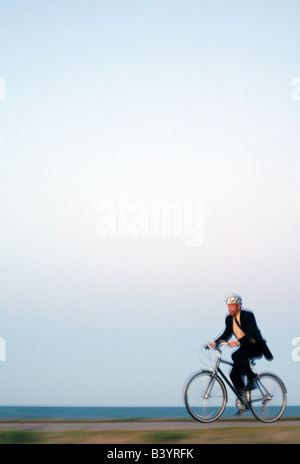 Man in suit rides bicycle along Chicago lake front - Stock Photo