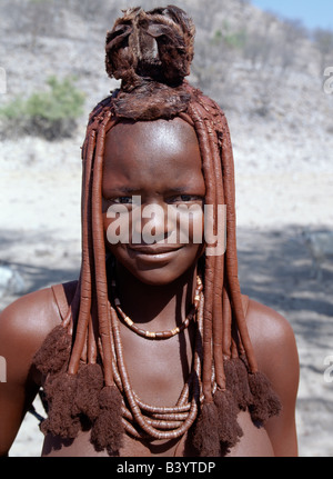 Namibia, Kaokoland, Epupa. A young Himba girl in traditional attire. Her body gleams from a mixture of red ochre, - Stock Photo