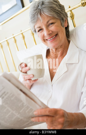 Woman in bedroom with coffee and newspaper smiling - Stock Photo