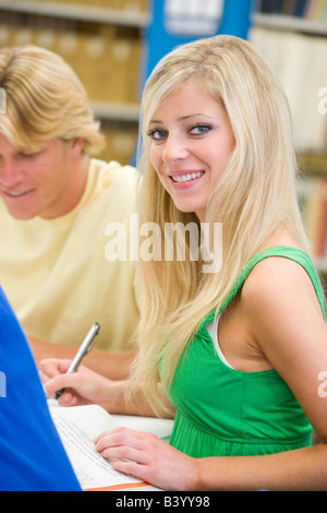 Three people in library studying (selective focus) - Stock Photo