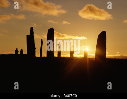 dh Standing stone circle RING OF BRODGAR ORKNEY People sitting watching a sunset holiday tourists uk visiting scotland - Stock Photo