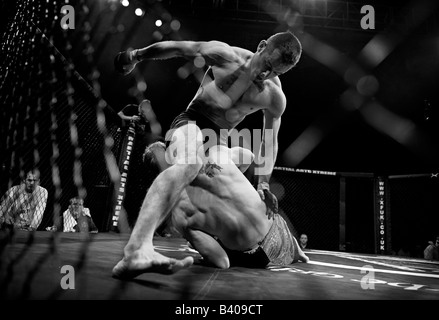 Cage fighter lands a punch on opponent. - Stock Photo
