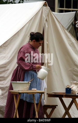 A women holding a water pitcher dressed and camping during the Civil War Encampment Reenactment - Stock Photo