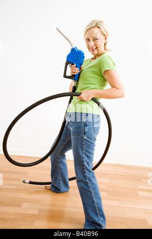 Portrait of adult blonde woman holding gas nozzle like a gunslinger