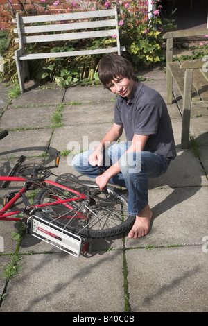 Teenage boy repairing bicycle puncture - Stock Photo