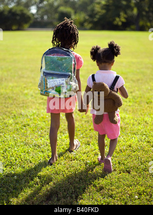 Two young girls carrying backpacks walking to school in Chicago park - Stock Photo