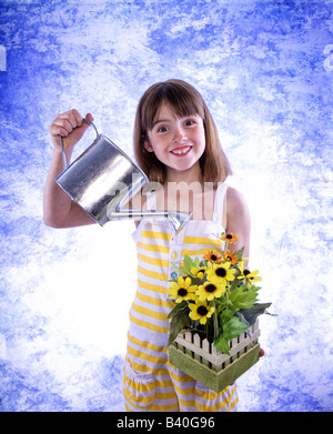 Funny young girl watering yellow daisy flowers with watering can on blue and white sky like background - Stock Photo