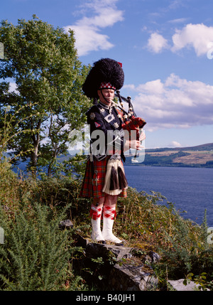 dh  SCOTTISH PIPER SCOTLAND Bagpipes tartan kilt bagpipe in highlands bag pipes player bagpiper traditional highland dress male loch ness