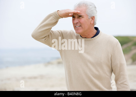 Man at the beach looking out with hand over eyes