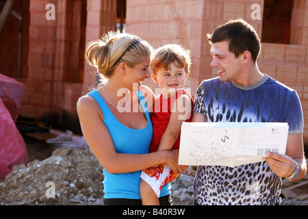 Family in front of shell of bulding - Stock Photo