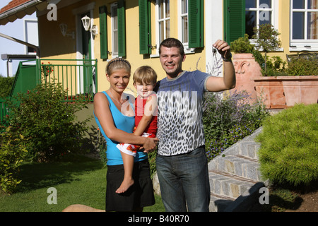 couple in front of newly bought house - Stock Photo