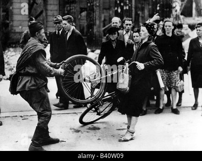 events, Second World War / WWII, Germany, end of war, Soviet soldier taking bicycle of a German woman, Berlin 1945, - Stock Photo