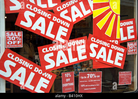 red and white closing down sale signs in a shop window in kingston upon thames, surrey, england - Stock Photo