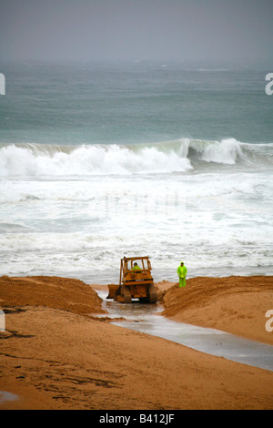 Earth moving machinery is used to release flood waters at Manly lagoon Australia during cyclonic weather - Stock Photo