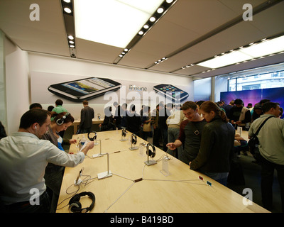 People looking at the new iPhone 3G in the very busy Apple store in Regent street London UK - Stock Photo