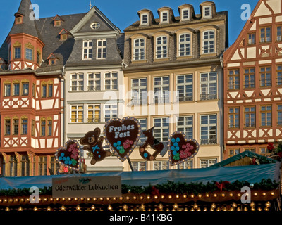 Christmas fair on the square Roemer Römer in front of storefronts of half timbered houses with booth for christmas - Stock Photo